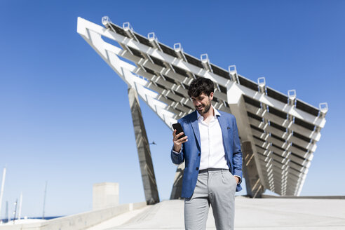 Young businessman looking at smartphone outdoors - GIOF02564