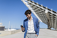 Young businessman looking at smartphone outdoors - GIOF02567