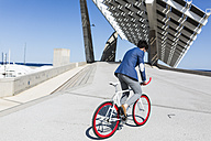 Young businessman on fixie bike outdoors - GIOF02573