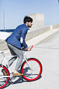 Young businessman on fixie bike outdoors - GIOF02576