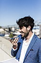 Happy young businessman with smartphone outdoors - GIOF02585