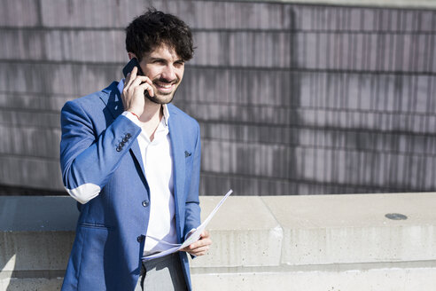 Smiling young businessman with smartphone and documents outdoors - GIOF02588