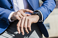 Close-up of businessman with smartwatch - GIOF02591