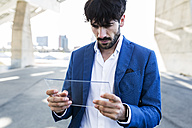 Young businessman holding futuristic portable device - GIOF02594