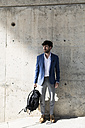 Young businessman standing at concrete wall - GIOF02600
