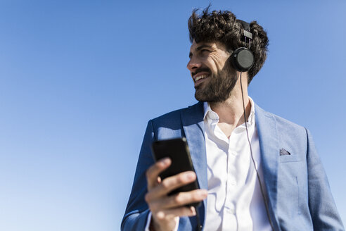 Young businessman with smartphone wearing headphones under blue sky - GIOF02603