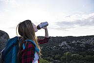 Spain, Madrid, young woman drinking during a trekking day - ABZF02010