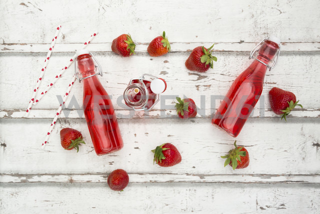 Three glass bottles of homemade strawberry lemonade and strawberries on white wood - LVF06105