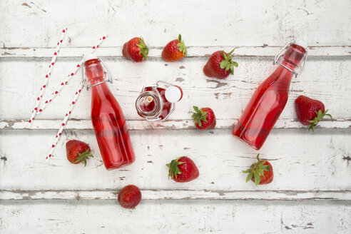 Three glass bottles of homemade strawberry lemonade and strawberries on white wood - LVF06105