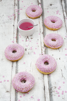 Six doughnuts with pink icing and sugar granules on wood - LVF06108