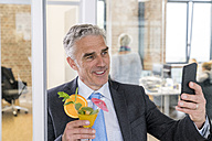 Mature businessman drinking cocktail while taking a selfie - FMKF04094