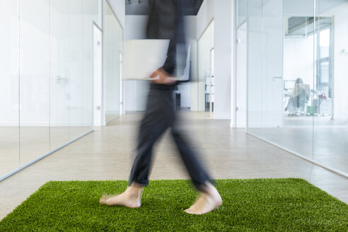 Mature businessman walking barefoot on grass carpet in office - FMKF04139