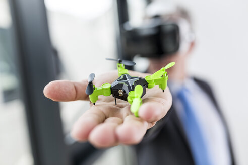 Mature businessman looking at drone through VR goggles - FMKF04142