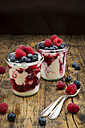 Two glasses of Greek yogurt with berry groats, fresh blueberries and raspberries on wood - LVF06114