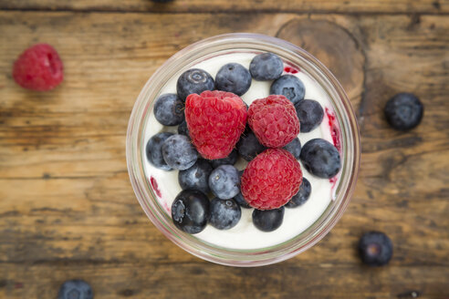 Glass of Greek yogurt with breey gorats, fresh blueberries and raspberries, close-up - LVF06117