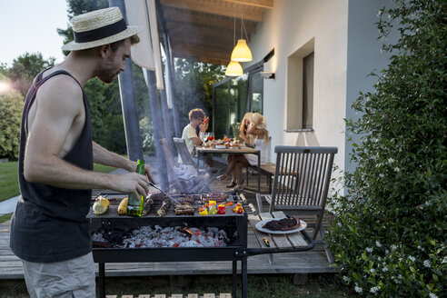 Man at barbecue grill with friends in background - ZOCF00358