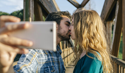 Couple in love taking selfie with smartphone while kissing - DAPF00753