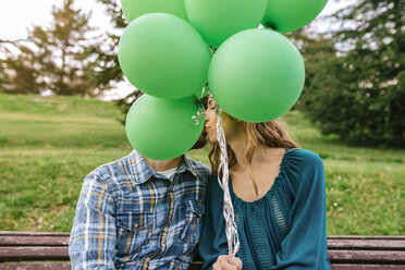 Young couple kissing behind green balloons - DAPF00762