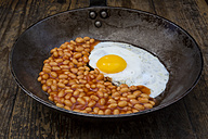 Fried egg and baked beans in frying pan on wood - LVF06124