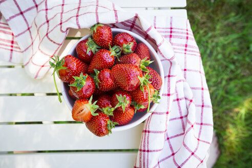 Bowl of strawberries and kitchen towel on garden table - LVF06129