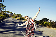 South Africa, Cape Town, Signal Hill, happy young woman with raised arms on country road - SRYF00518