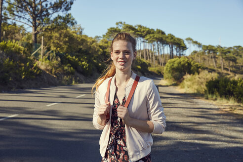 South Africa, Cape Town, Signal Hill, smiling young woman with backpack on country road - SRYF00524
