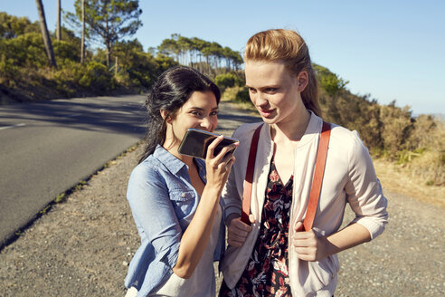 South Africa, Cape Town, Signal Hill, two young women with cell phone on a trip - SRYF00527