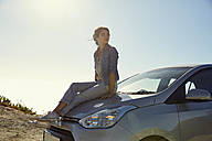 Young woman sitting on a car looking around - SRYF00536