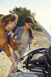 Two young women checking their car standing at the roadside - SRYF00542