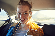 Smiling young woman on the back seat of a car - SRYF00545