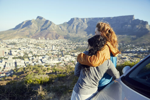 South Africa, Cape Town, Signal Hill, two young women leaning against car overlooking the city - SRYF00548