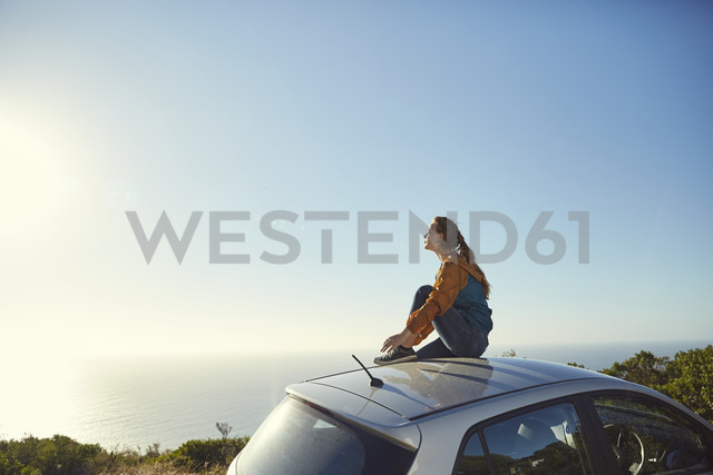 South Africa, Cape Town, Signal Hill, young woman sitting on top of car enjoying the view to the sea - SRYF00551 - Martina Ferrari/Westend61