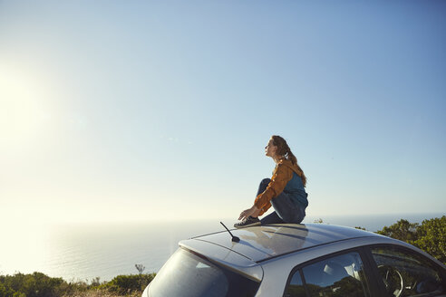 South Africa, Cape Town, Signal Hill, young woman sitting on top of car enjoying the view to the sea - SRYF00551