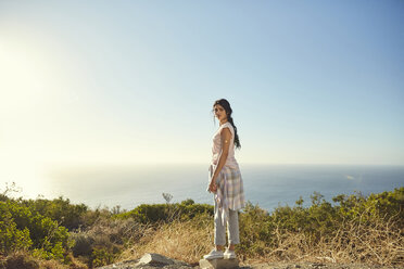 South Africa, Cape Town, Signal Hill, young woman standing at the coast - SRYF00557