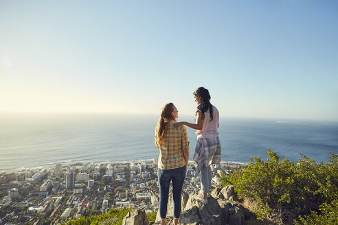South Africa, Cape Town, Signal Hill, two young women overlooking the city and the sea - SRYF00560