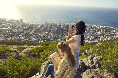 South Africa, Cape Town, Signal Hill, two young women with map and binoculars overlooking the city and the sea - SRYF00563
