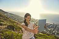 South Africa, Cape Town, Signal Hill, young woman above the city taking a selfie with tablet - SRYF00566
