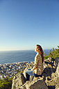 South Africa, Cape Town, Signal Hill, young woman sitting on rock with view to the city and the sea - SRYF00569