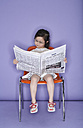 Portrait of little girl sitting on chair with newspaper - FS00901