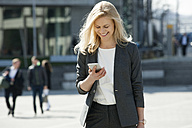 Portrait of smiling blond businesswoman looking at cell phone - CHAF01876