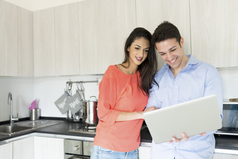 Smiling couple with laptop in kitchen - FMOF00281
