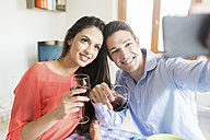 Couple holding red wine glasses posing for a selfie - FMOF00284