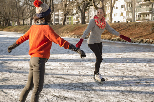 Female friends ice skating on canal - MFF03514