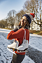 Happy woman on canal carrying ice skates - MFF03520