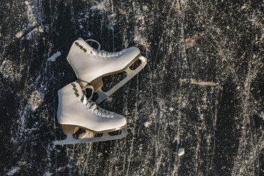 Ice skates lying on frozen water surface with skate traces - MFF03523