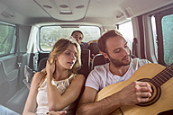 Man with friends in a car playing guitar - ZOCF00377