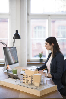 Architectural model and woman working at desk in office - FKF02241