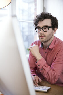 Confident man in office looking at computer screen - FKF02259