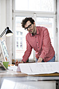 Man working on blueprint at desk in office - FKF02262