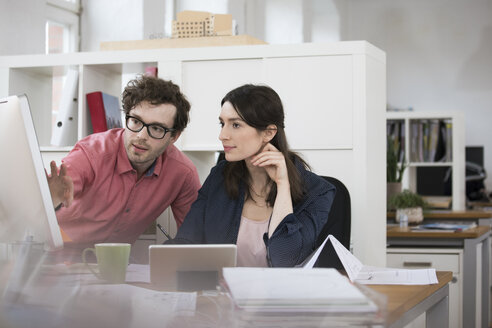 Man and woman discussing at desk in office - FKF02265